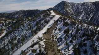 AX0009_068 - 5K stock footage aerial video approach top of snowy ski run at the Mount Baldy Ski Lifts in the San Gabriel Mountains, California
