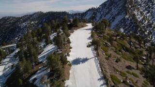 AX0009_069 - 5K stock footage aerial video fly over a snowy ski run at Mount Baldy Ski Lifts, California in winter