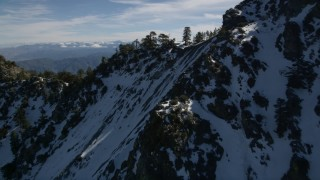 AX0009_070 - 5K stock footage aerial video fly over trees on top of frozen ridge in the San Gabriel Mountains in wintertime, California
