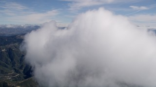 AX0009_073 - 5K stock footage aerial video of flying through a small cloud over the San Bernardino Mountains, California