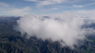AX0009_075 - 5K stock footage aerial video of approaching a cloud over the San Bernardino Mountains, California
