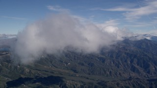 AX0009_079 - 5K stock footage aerial video of flying through clouds over the San Bernardino Mountains, California