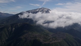 AX0009_086 - 5K stock footage aerial video of approaching clouds near a snowy peak in the San Bernardino Mountains, California