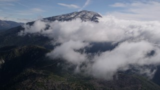 AX0009_087 - 5K stock footage aerial video approach clouds near snowy peak in San Bernardino Mountains of California