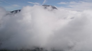 AX0009_089 - 5K stock footage aerial video fly over a cloud near a peak with winter snow in the San Bernardino Mountains, California