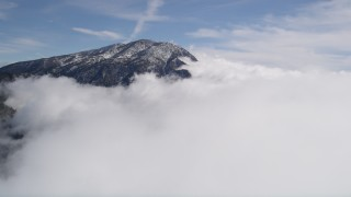 AX0009_090 - 5K stock footage aerial video approach clouds circling a San Bernardino Mountains peak in winter, California