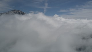 AX0009_093 - 5K aerial stock footage video of thick clouds by a snowy peak in the San Bernardino Mountains in winter, California