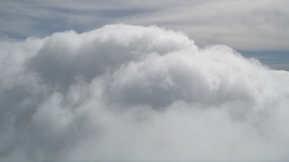AX0009_101 - 5K stock footage aerial video fly over thick clouds to reveal summit of San Bernardino Mountains peak, California