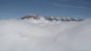 AX0009_105 - 5K stock footage aerial video orbit clouds to reveal snowy summits in San Bernardino Mountains in winter, California