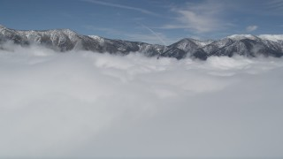 AX0009_107 - 5K stock footage aerial video fly over clouds to approach snowy San Bernardino Mountains in winter, California