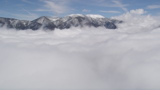 AX0009_108 - 5K stock footage aerial video tilt up from clouds to reveal snowy San Bernardino Mountains, California