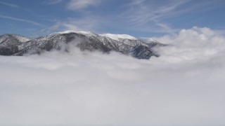 AX0009_110 - 5K stock footage aerial video approach snowy San Bernardino Mountains and fly over clouds in winter, California