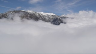 AX0009_111 - 5K stock footage aerial video fly over clouds and approach snowy San Bernardino Mountains in wintertime, California