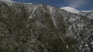 AX0009_115 - 5K stock footage aerial video tilt up a San Bernardino Mountains slope with light winter snow, California