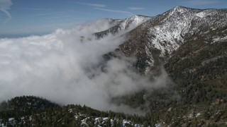 AX0009_119 - 5K stock footage aerial video of clouds blanketing snowy mountain slopes in the San Bernardino Mountains, California