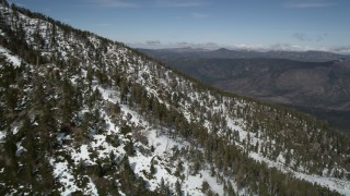 AX0009_123 - 5K stock footage aerial video fly over a frozen mountain slope to reveal evergreen forest valley, San Bernardino Mountains, California