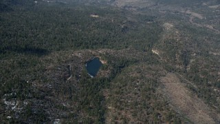 AX0009_125 - 5K stock footage aerial video orbit small lake and evergreen forest with winter snow in the San Bernardino Mountains, California