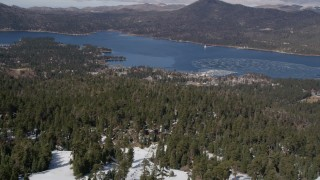 AX0009_129 - 5K stock footage aerial video fly over snowy mountain and ski lift to reveal Big Bear Lake in winter, California