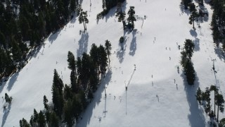 AX0009_132 - 5K stock footage aerial video orbit skiers on a steep slope with winter snow at the Snow Summit Ski Resort, California