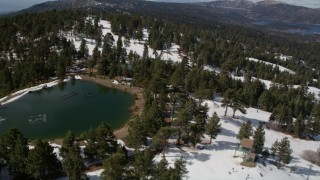 AX0009_135 - 5K stock footage aerial video orbit ski runs and a small lake on a snowy mountain at Snow Summit, California