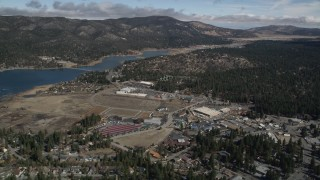 AX0009_139 - 5K stock footage aerial video orbit lakeside shopping center in the small town of Big Bear Lake, California in winter