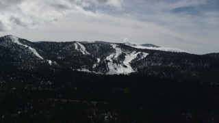 AX0009_142 - 5K stock footage aerial video of Snow Summit ski slopes with winter snow, California