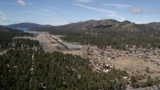 AX0009_143 - 5K stock footage aerial video orbit and approach the runway at Big Bear City Airport, California
