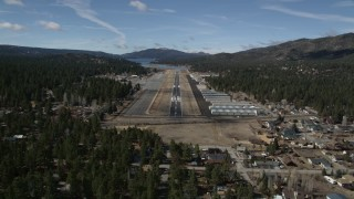 AX0009_143E - 5K stock footage aerial video orbit and approach the runway at Big Bear City Airport, California