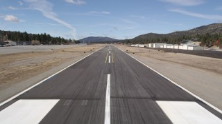 AX0009_144 - 5K stock footage aerial video approach the runway at Big Bear City Airport for a landing, California