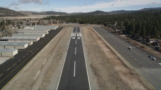 AX0010_001 - 5K stock footage aerial video liftoff from the eunway at Big Bear City Airport, California