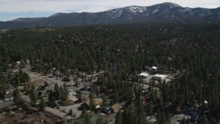 AX0010_002 - 5K stock footage aerial video approach forest with snow at the edge of Big Bear Lake, California