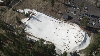 AX0010_006 - 5K stock footage aerial video approach people sliding down a frozen slope at Big Bear Lake in winter, California