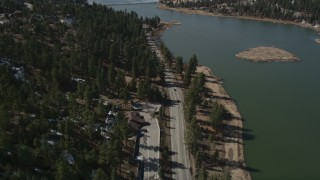 AX0010_007 - 5K stock footage aerial video tilt up to reveal Big Bear Lake near patches of light winter snow, California