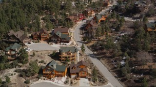 AX0010_010 - 5K stock footage aerial video orbit and fly over homes near Big Bear Lake with patches of winter snow, California