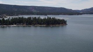 AX0010_014 - 5K stock footage aerial video of approaching lakeside homes at Big Bear Lake with patches of light winter snow, California