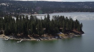AX0010_015 - 5K stock footage aerial video orbit homes on the shore of Big Bear Lake with patches of light winter snow, California