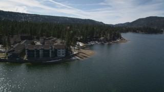 AX0010_019 - 5K stock footage aerial video orbit apartment building and homes on the shore of Big Bear Lake with winter snow, California