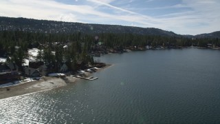AX0010_020 - 5K stock footage aerial video of lakeshore homes with light winter snow at Big Bear Lake, California