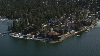 AX0010_025 - 5K stock footage aerial video orbit large waterfront homes on the shore of Big Bear Lake with light winter snow, California