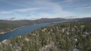 AX0010_028 - 5K stock footage aerial video pan across snowy mountain and forest to reveal Big Bear Lake in winter, California