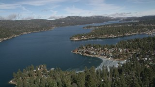 AX0010_029 - 5K stock footage aerial video fly over a mountain slope to reveal Big Bear Lake in winter, California