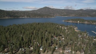 AX0010_032 - 5K stock footage aerial video of Big Bear Lake seen from town on the shore in winter, California