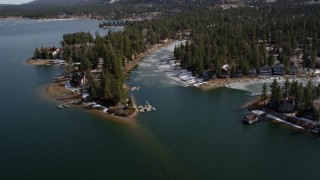 AX0010_034 - 5K stock footage aerial video orbit homes on the ice shore of Big Bear Lake in winter, California