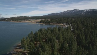 AX0010_036 - 5K stock footage aerial video tilt to reveal and approach shore of Big Bear Lake with light winter snow, California