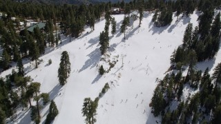 AX0010_044 - 5K stock footage aerial video of flying over skiers and a ski lift at Snow Summit Ski Resort in wintertime, California