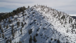 AX0010_067 - 5K stock footage aerial video fly over snowy mountains to approach low cloud bank in the San Bernardino Mountains, California