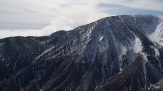 AX0010_068 - 5K stock footage aerial video orbit snowy peak in the San Jacinto Mountains in winter, California