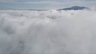 AX0010_073 - 5K stock footage aerial video approach clouds and a tall San Jacinto Mountains peak in the distance, California