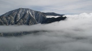 AX0010_090 - 5K stock footage aerial video orbit summit of a peak with light snow in the San Jacinto Mountains, California