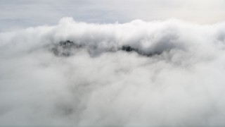 AX0010_091 - 5K stock footage aerial video approach mountain summit covered by clouds in the San Jacinto Mountains, California